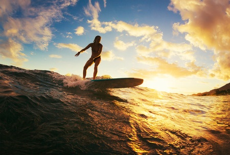 43374713 - surfing at sunset. beautiful young woman riding wave at sunset. outdoor active lifestyle.