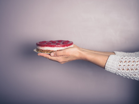 45138921 - female hands holding a rapberry cheesecake against a purple wall