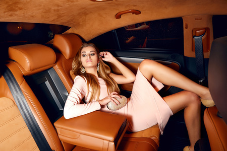 51002676 - beautiful young sexy blonde wearing evening makeup in elegant fitting dress fashionable stylish sitting in cabin of expensive car comes out of it in hand handbag luxury rich life going party concert