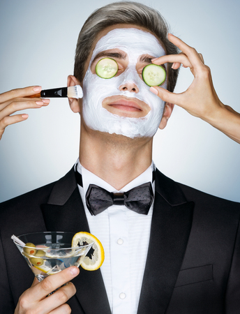 62173388 - gentleman receiving spa facial treatment. photo of handsome man with a facial mask on his face and cucumber on his eyes. grooming himself